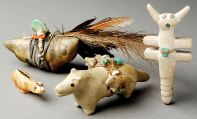 Zuni fetishes, Counterclockwise from top left: Coyote, c. 1950, by Teddy Weahkee. Zuni rock, turquoise, coral, shell, sinew, feathers, 4.4 cm x 15.9 cm. Badger, c. 1940 by Leo Poblano. Nutria rock. 1.3 cm x 4.4 cm. Wolf, c. 1940 by Leekya Deyuse. Zuni rock, turquoise, shell, sinew. 3.8 cm x 8.9 cm. Dragonfly, c. 1935 by Theodore Kucate. Ojo rock, turquoise. 7.6 cm x 3.8 cm. Leonora Scott Curtin Collection, Wheelwright Museum of the American Indian. Photo by Addison Doty.